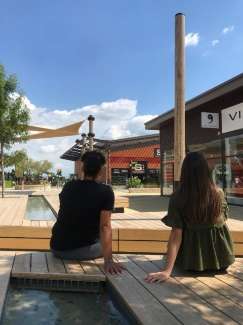 euroform w - sustainable street furniture - seating island in shopping centre - modular seating with shade sail, trees and water - wooden lounger with shade dispenser - bench with indirect lighting